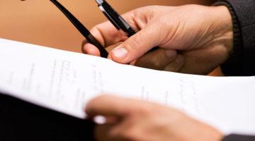 Händer som håller i ett dokument, en penna och ett par glasögon