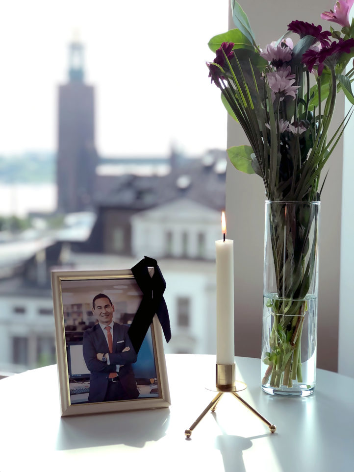 Photo of deceased Mårten Lindeborg with a lit candle and a flower