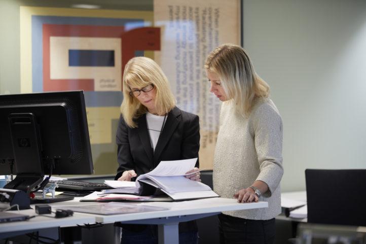 Två medarbetare tittar i en pärm
