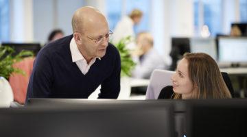 Två kollegor i samtal framför dator