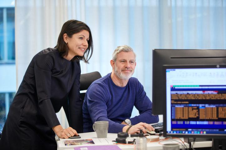 AP3 medarbetare pratar vid en dator